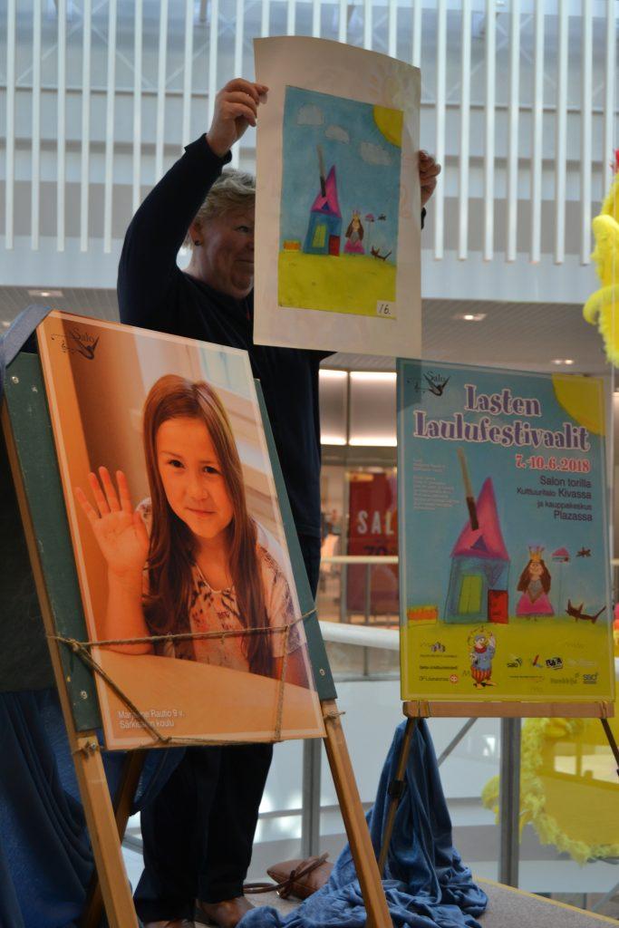 Kuva jossa on Marjanne Rautio ja piirros sekä juliste. Piirrosta pitelee Pirjo Sinervo.